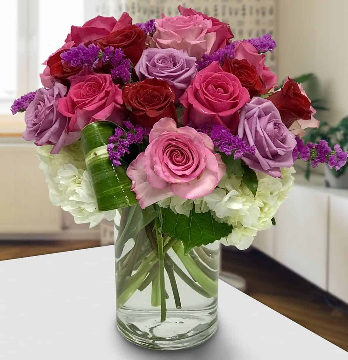 several different shades of red, pink and purple roses atop a bed of white hydrangea with purple stock laced throughout.